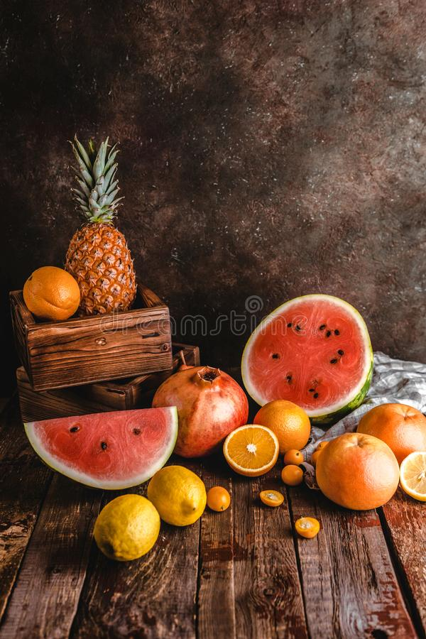 slices of watermelon, oranges, pomegranate, pineapple and kumquats on rustic royalty free stock photography