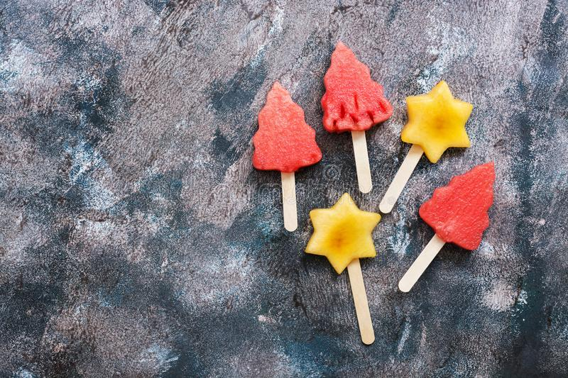 Slices of watermelon in the shape of Christmas trees on a stick. Slices of peach in the shape of a star on a stick.. Fruit on a st stock photo
