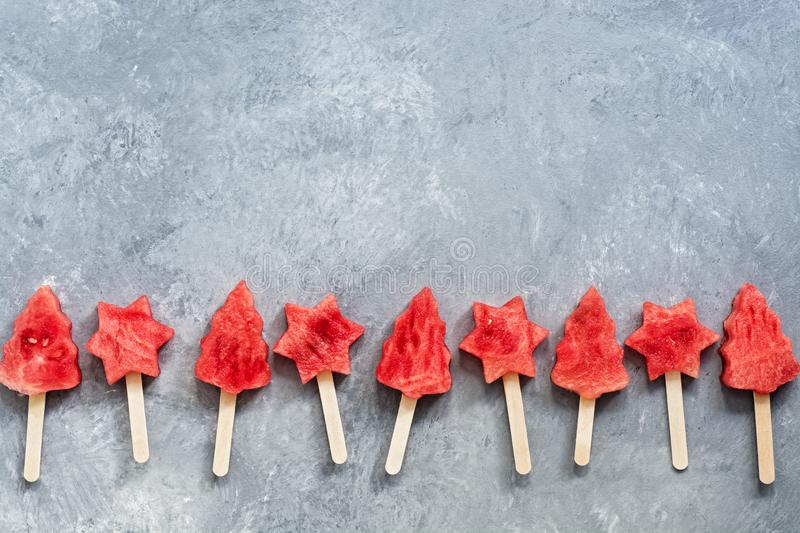 Slices of watermelon on a stick in the shape of a Christmas tree and stars on a gray background. Popsicles in a row. Top view, royalty free stock photo