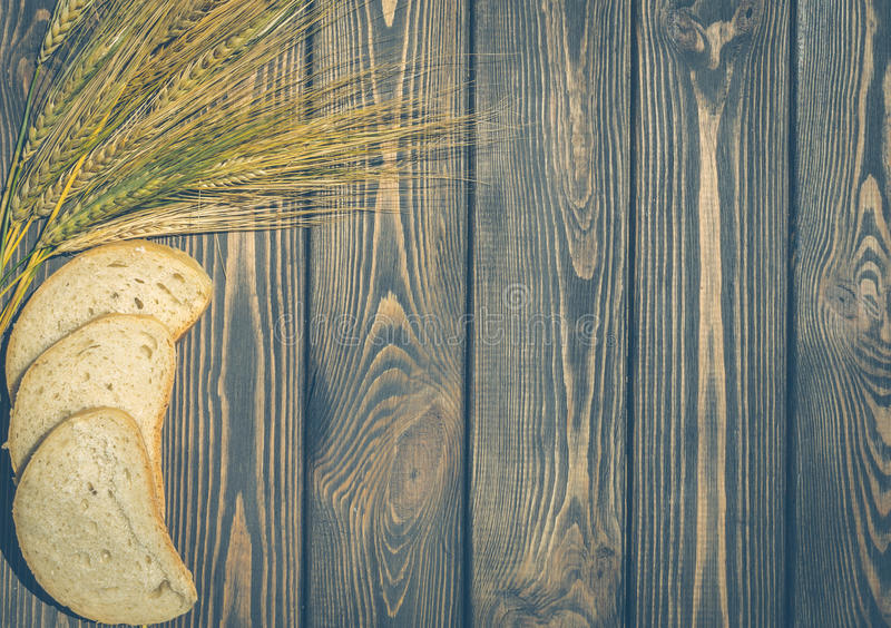 Slices of wheat bread and wheat ears royalty free stock photo