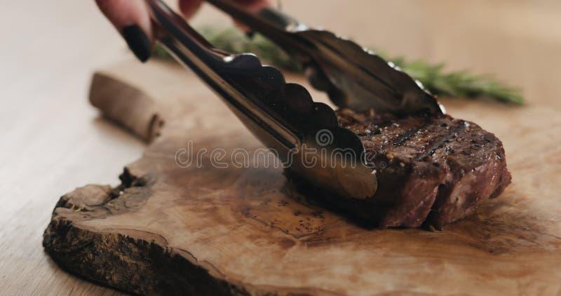 Slicing medium rare fillet mignon steak on wood board stock photos