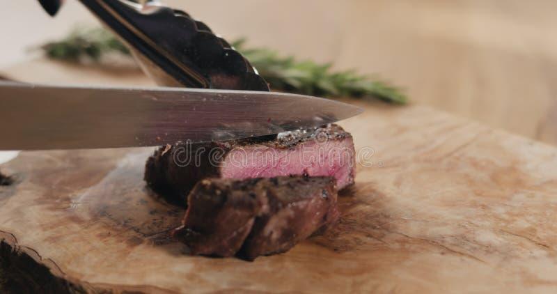 Slicing medium rare fillet mignon steak on wood board stock images