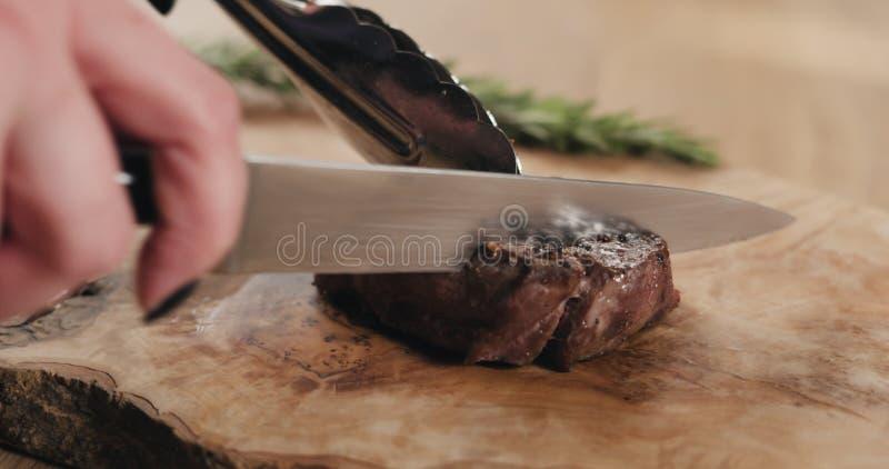 Slicing medium rare fillet mignon steak on wood board stock photography