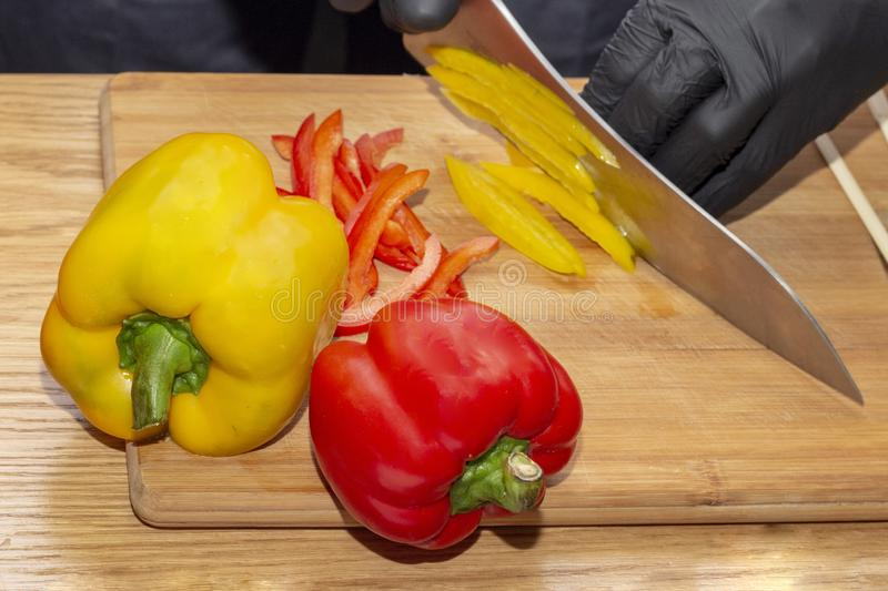 Slicing paprika cook. cooking healthy food diet healthy food. wooden cutting board on wooden table, chef hands in black rubber glo stock photography