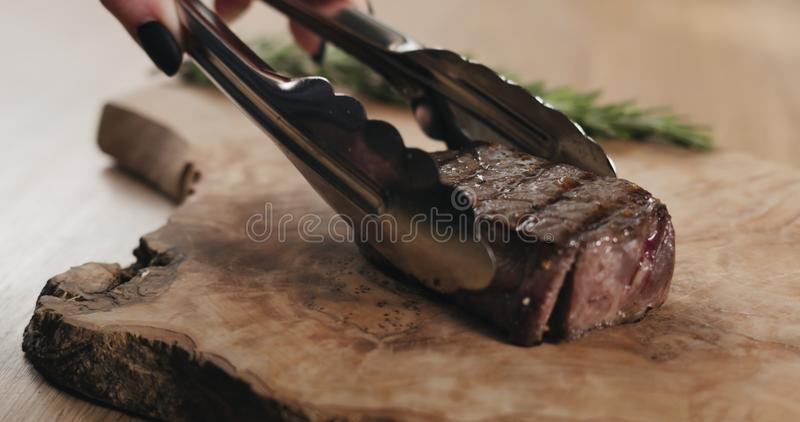 Slicing rare fillet mignon steak on wood board royalty free stock image