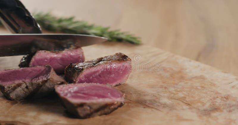 Slicing rare fillet mignon steak on wood board stock images