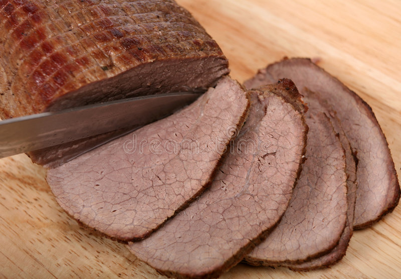 Slicing a round beef joint stock image