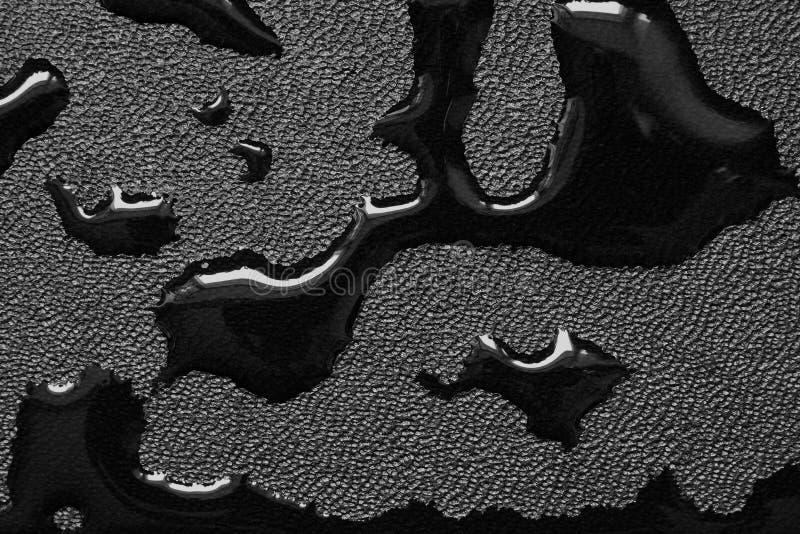 Slicks de óleo na tela de couro preta imagem de stock