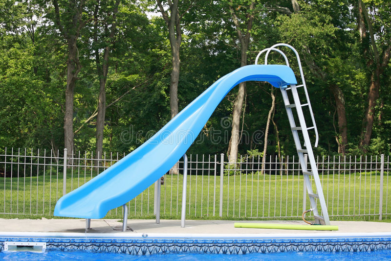 Slide in a In Ground Pool. Blue Slide in a In Ground Pool royalty free stock photography