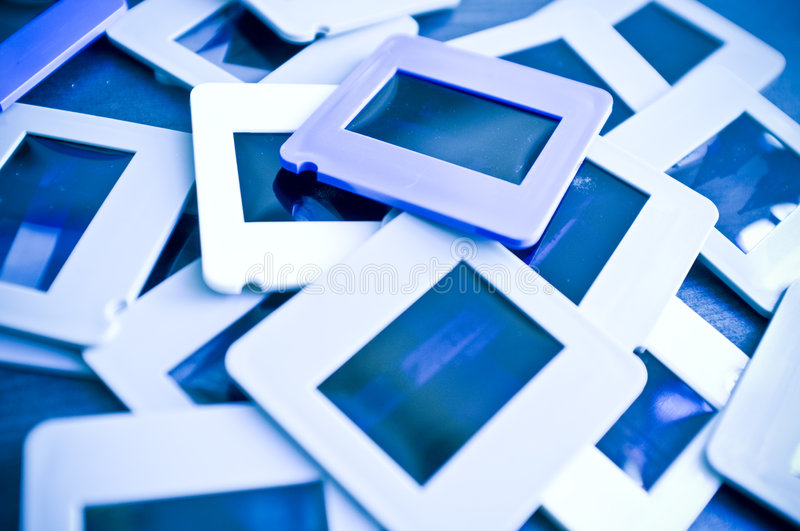 Slide holders. A closeup view of a pile of plastic 35mm slide film holders or frames. Blue tone royalty free stock photos