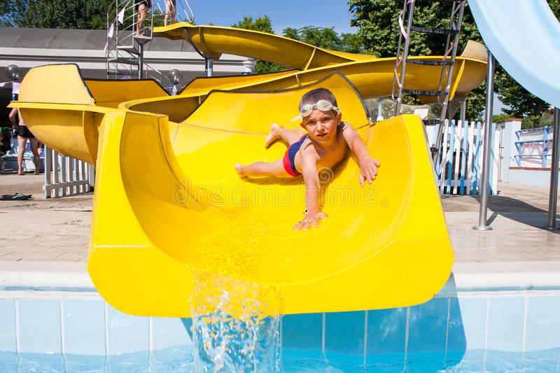 Slide in the pool. Happy child playing with the slide in the pool royalty free stock images