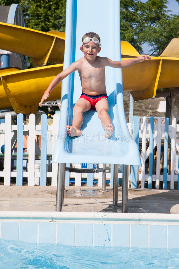 Slide in the pool. Happy child playing with the slide in the pool royalty free stock photos