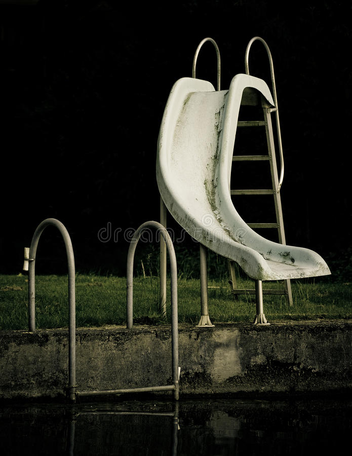 Slide into a swimming pool. A slide going into a dark swimming pool royalty free stock images