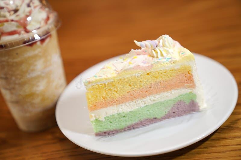 Slided tęcza tort dekoruje z jednorożec rogiem na wierzchołku obok kawowego frappe Tort jest w białym dysku na drewnianym stole i obraz stock