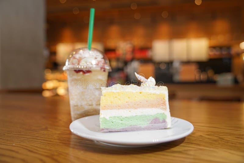 Slided t?cza tort dekoruje z jednoro?ec rogiem na wierzcho?ku obok kawowego frappe Tort jest w bia?ym dysku na drewnianym stole i obraz stock