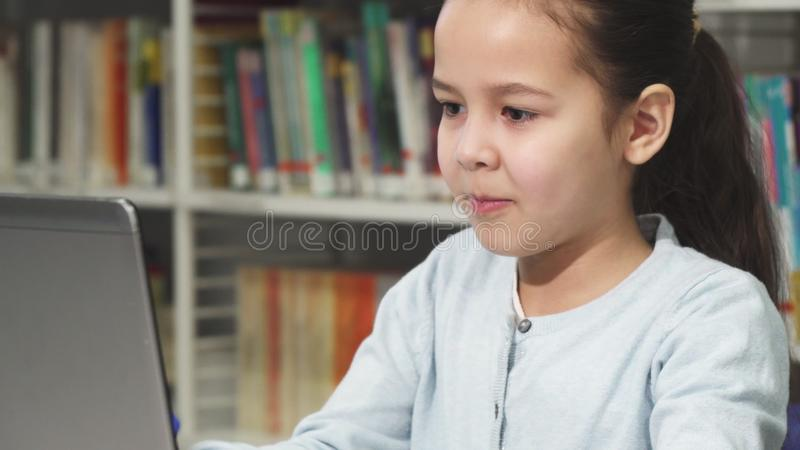Close up of a pretty little Asian girl typing on the laptop royalty free stock images