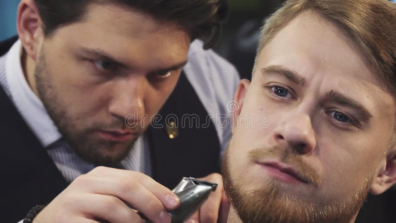 Close up of a professional barber trimming beard of a young man royalty free stock photo