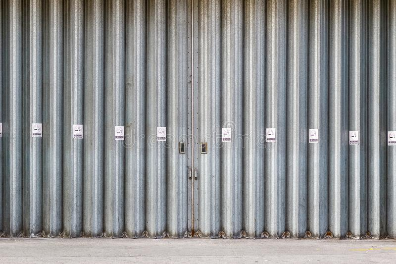 Sliding and folding industrial doors with No Smoking signs royalty free stock image