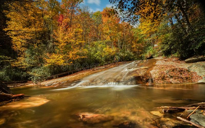 Sliding Rock Falls in the Appalachians of North Carolina in late autumn with fall color foliage. And natural swimming pool in the foreground royalty free stock images