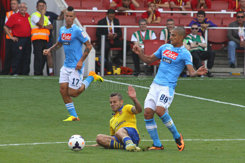 Sliding tackle in the Emirates Cup. Sliding tackle on Gokhan Inler during the match Arsenal-Napoli for the Emirates Cup 2013, played in London on the 3rd of stock photography
