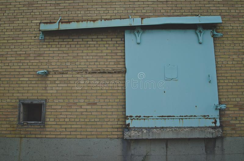 The sliding teal door on the old factory royalty free stock photo