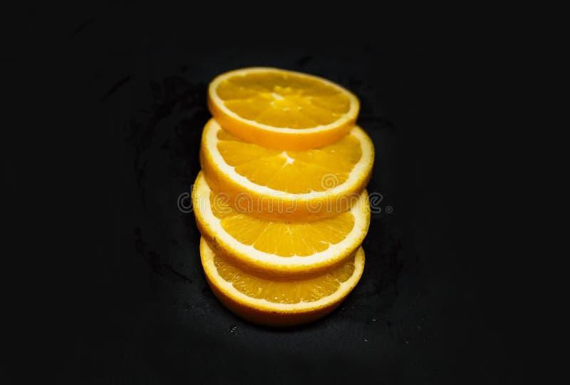 Slieces oranges juteux de Fpur sur le fond noir photographie stock