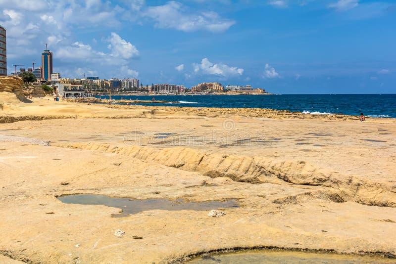 Sliema rocky beach and St. Julian`s skyline royalty free stock photos