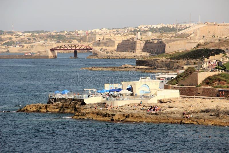 Sliema, Malte, juillet 2014 Les équipements côtiers de l'île, de la plage rocheuse et des personnes de repos photo stock