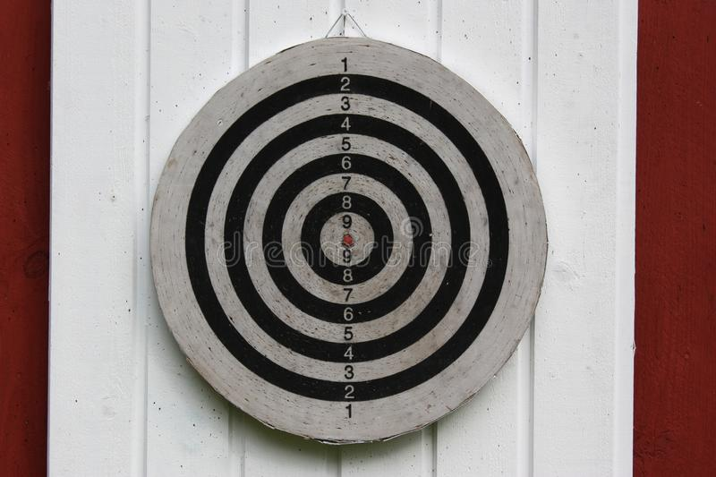 Slight closeup shot of a dartboard hanged on a white and red wall stock photography