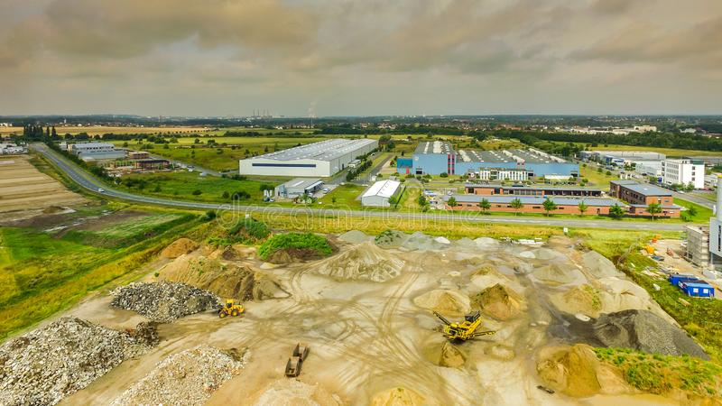 Slightly alienated aerial view of an industrial area, with a warehouse for building materials in the foreground, large factory royalty free stock image