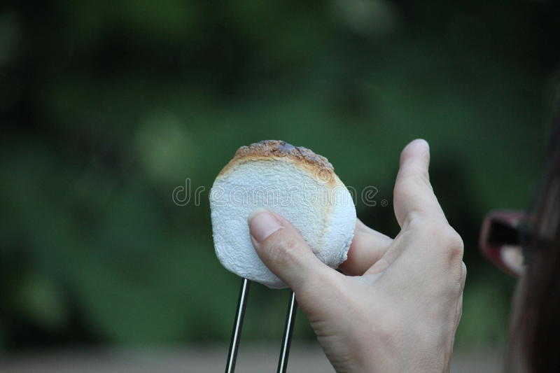 Slightly browned smores. With a hand checking it. White smores with a greenish blurred background royalty free stock image