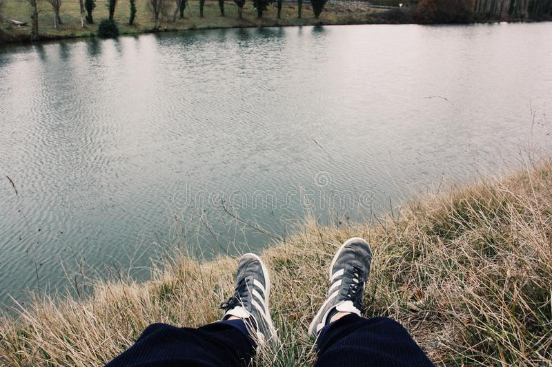 Slightly closeup shot of a person wearing sneakers sitting on grass by the lake. A slightly closeup shot of a person wearing sneakers sitting on grass by the royalty free stock photo