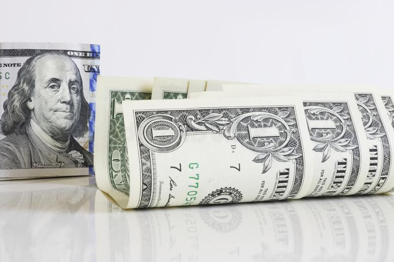 Slightly curled one-dollar bills on a light background close-up. In the background, President Franklin on a 100-dollar bill. stock photo