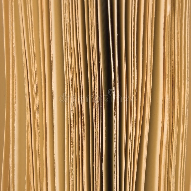 Slightly open book pages background sepia, large vertical macro closeup studio shot. Slightly open book pages background sepia large vertical macro closeup royalty free stock photo