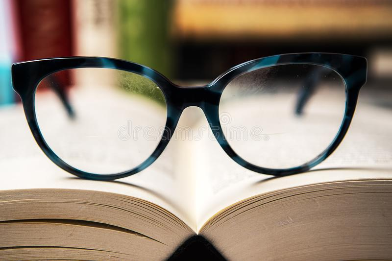 Slightly smudged Eyeglasses with blue frame on open book with blurred books in background. Reading learning concept royalty free stock photo