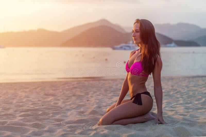 Slim загорело модель в бикини представляя на песке пляжа сидя в свете утра на восходе солнца с горами и морем внутри стоковое изображение