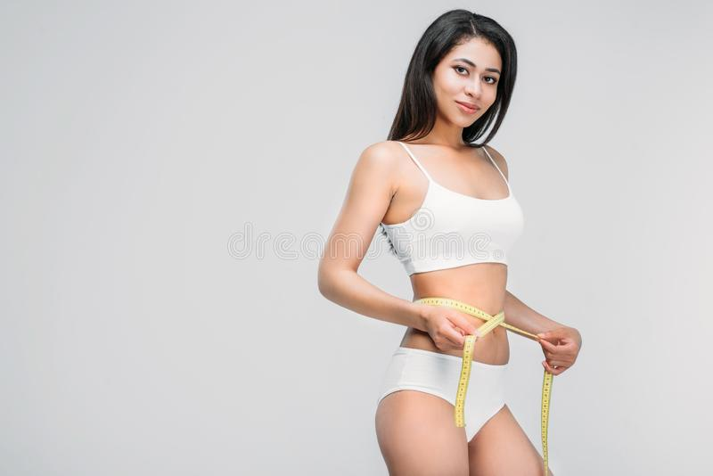 Slim african american girl in underwear measuring her waistline. Isolated on grey royalty free stock image