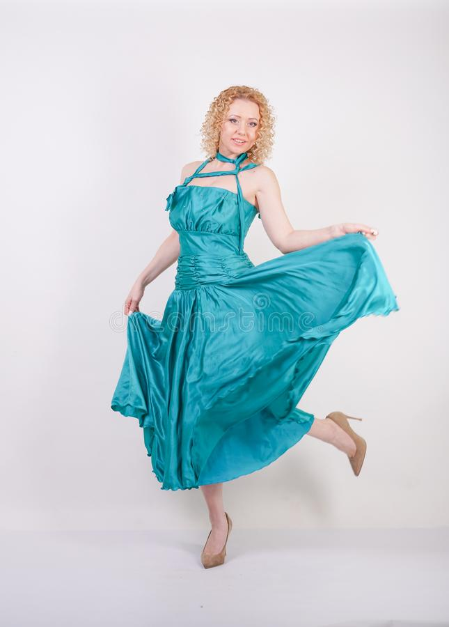 Slim airy girl in flying blue evening dress on white background in Studio royalty free stock photos