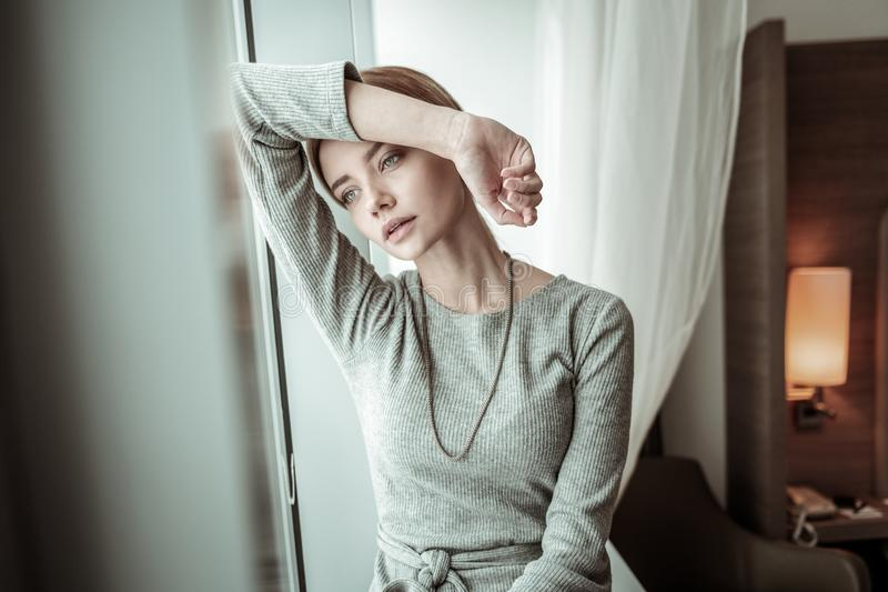 Slim appealing blonde-haired woman sitting near window stock image