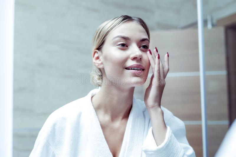 Slim appealing woman feeling good taking care of her face skin stock image