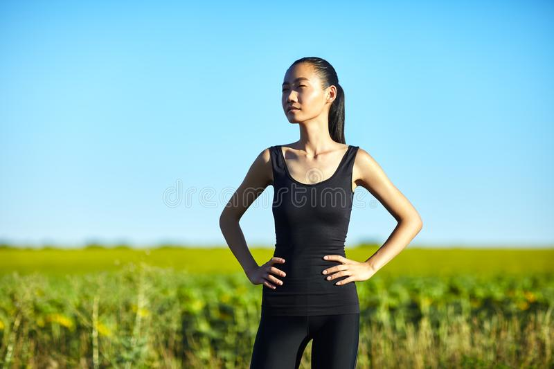 Slim athletic Asian woman resting in field in summer day stock photography