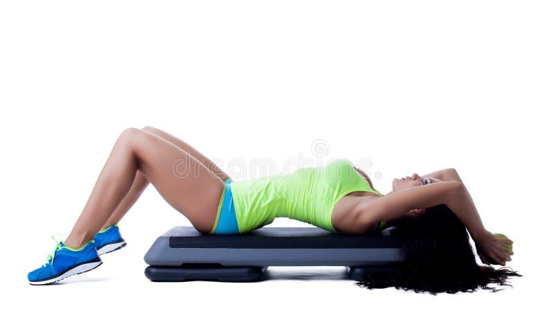 Slim athletic brunette doing aerobics on stepper. On white stock images
