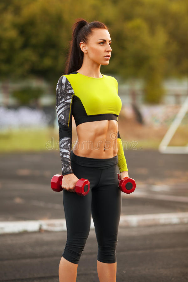 Slim athletic woman with dumbbells in the stadium. Sporty girl with flat belly workout, outdoors royalty free stock images