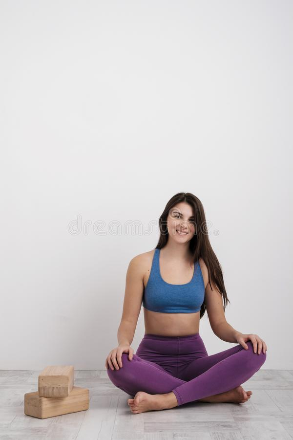 Young brunette woman in purple leggings and a sports t-shirt does exercises on the floor. Balances on the blocks and royalty free stock photography
