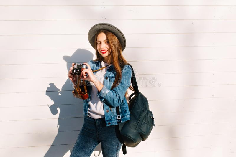 Slim attractive brunette girl in hat with stylish black leather backpack posing holding camera. Gorgeous young long royalty free stock photos