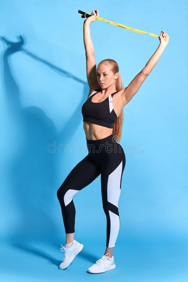 Slim awesome good looking woman training with jump rope stock photography