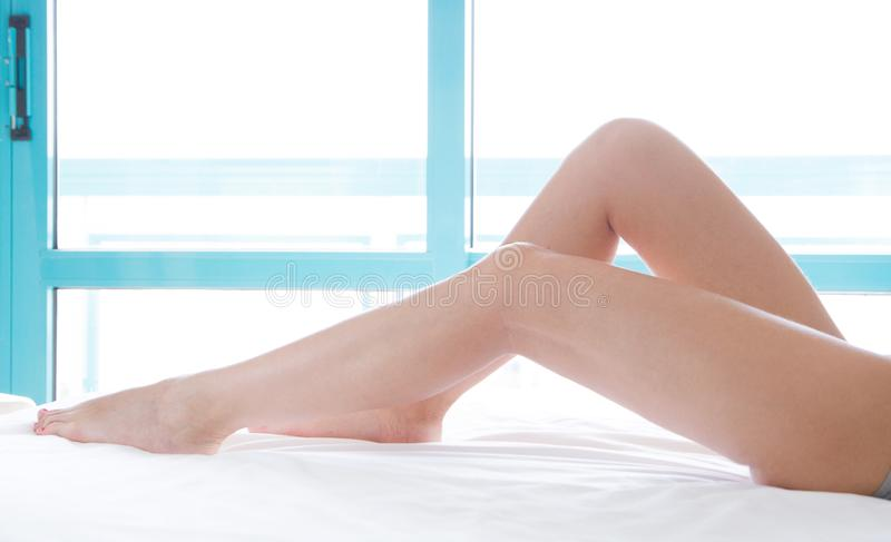 Slim beautiful female legs on bed. Cropped image of erotically lying on bed beautiful woman in bedroom. Crumpled white bedclothes. Slim beautiful female legs on stock photo