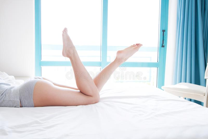 Slim beautiful female legs on bed. Cropped image of erotically lying on bed beautiful woman in bedroom. Crumpled white bedclothes. royalty free stock photography