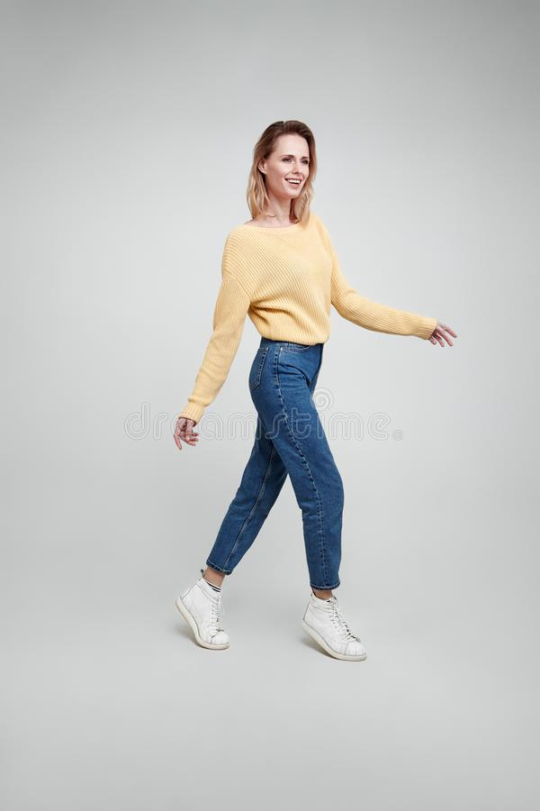 Slim and beautiful. Full length studio shot of attractive young woman in casual wear keeping hand on the air and smiling walking. Against grey background royalty free stock photography