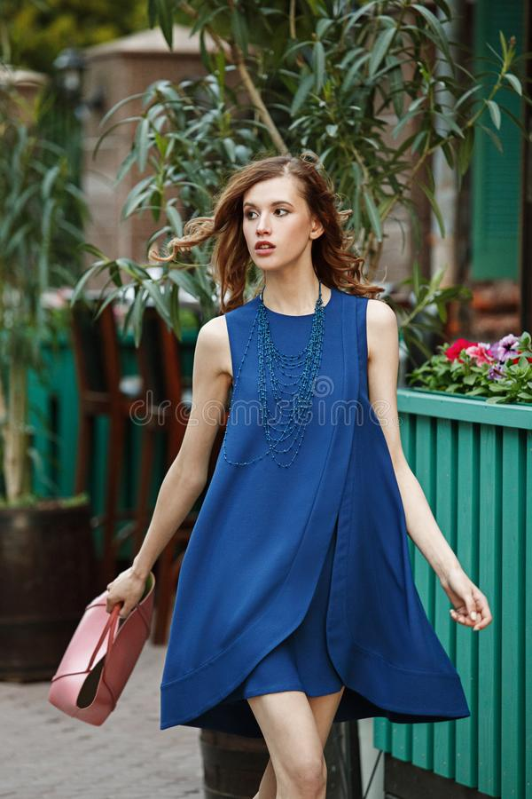 Slim beautiful girl dressed in a blue summer dress holding a pink bag is walking in a city street on a warm day stock photography